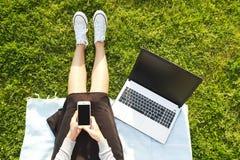 Studentmädchen, das auf dem grünen Rasen tut Hausarbeit auf ihrer Laptop-Computer sitzt Junge Frau, die am blogging Park, wr sitz Stockfotografie
