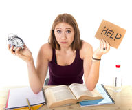 Studentmädchen im Druck bitten um die Hilfe, die Weckerzeit-Prüfungskonzept hält Stockbilder