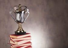 Studentmästareutmärkelse med exponeringsglas på högen av böcker royaltyfri foto
