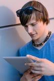 Studentpojke med minnestavlabenägenhet mot väggen Arkivbild