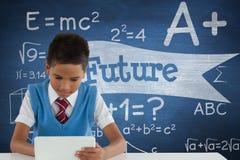 Studentpojke på tabellen genom att använda en minnestavla mot den blåa svart tavla med framtida text Arkivbilder