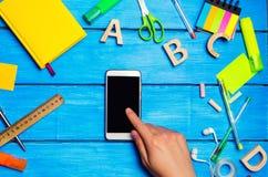 Studentpunkter till telefonen, den digitala dagboken eller eBooken, motvillighet som ska läras, skolatillförsel på en blå bakgrun royaltyfri foto