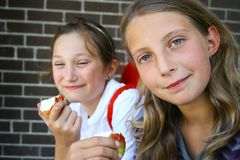 Students. Two young preteens eating apples at school Stock Photography