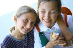 Students. Smiling preteens friends with apples at school Royalty Free Stock Photography