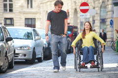 Students. Boy is walking next to a girl on a wheelchair Stock Images