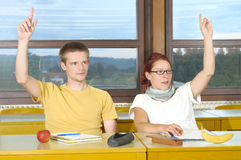 Students. In the classroom raising hands Stock Photo