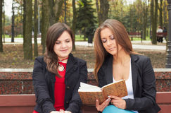Students. Two young girls on a bench reading a book Stock Photos