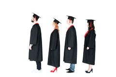 Students in academic caps and graduation gowns standing in a row Royalty Free Stock Photo