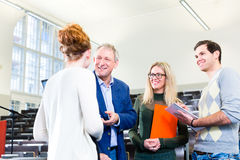 Students asking professor in college auditorium Royalty Free Stock Photography