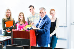 Students asking professor in college auditorium. College students making lesson notes while asking professor in university auditorium Royalty Free Stock Photos