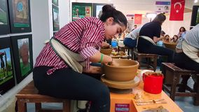 Students attending to the pottery contest at the 12th International Eskisehir Terra Cotta Symposium. Eskisehir, Turkey - September 08, 2018: Students attending stock video footage