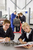 Students with auto part studying automotive trade in vocational school royalty free stock images
