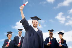 Students or bachelors with diplomas over blue sky Royalty Free Stock Photography