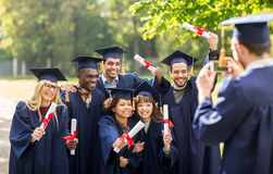Students or bachelors photographing by smartphone Royalty Free Stock Photos