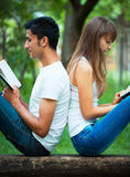 Students back to back reading a book outdoors Stock Photography