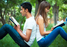 Students back to back reading a book outdoors Stock Photos