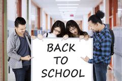 Students with Back to School text in corridor Stock Image