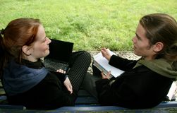Students on a bench. Two students chatting on a bench. Young man with a notepad, books and pen, woman with a laptop Stock Image