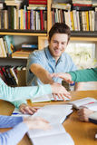 Students with books and hands on top in library Royalty Free Stock Image