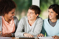 Students With Books And Laptop Looking At stock image