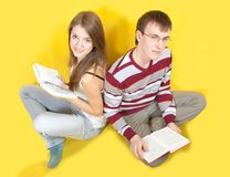 Students with books  over a yellow Stock Photo