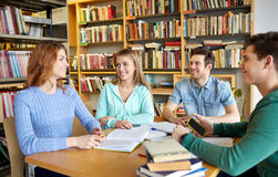 Students with books preparing to exam in library. People, knowledge, education and school concept - group of happy students reading books and preparing to exam Stock Photo