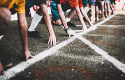 Students boy get set to leaving the starting for running competition boy at school sports day. Royalty Free Stock Images