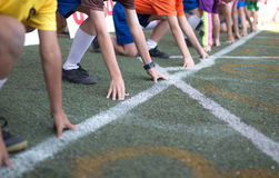Students boy get set to leaving the starting for running competition boy at school sports day. Royalty Free Stock Image