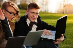 Students, boy and girl browsing in sunny park Stock Images