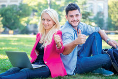 Students break. Student girl and boy student hold a laptop and l. Ooking at the camera while sitting on the grass near the campus of the University at the break Stock Image
