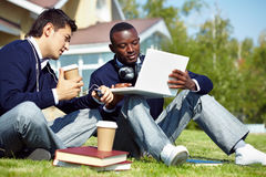 Students at break. Two male students sitting in campus and surfing internet on laptop Stock Photos