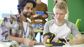 Students building a robotic arm stock video