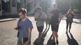 Students busy with smartphones on univesity campus stock video footage