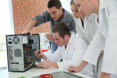 Students in calss fixing computer Royalty Free Stock Image