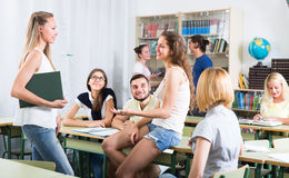 Students chatting while sitting in the room. Friendly adult students chatting while sitting in the room stock photos