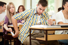 Students cheating with cheat sheet Royalty Free Stock Image