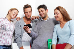 Students checking smartphone. Students checking social network status updates on smartphone Royalty Free Stock Photos