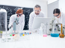 Students in chemistry lab. General-view of two students in a chemistry lab analyzing under microscope under supervision of a teacher Stock Image