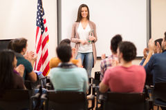 Students clapping hands to young satisfied assistant. Satisfied assistant finished teaching and her students clapping hands Royalty Free Stock Photo