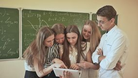Students in the class discuss something on the laptop. Against the background of a school board with mathematical. Formulas stock video