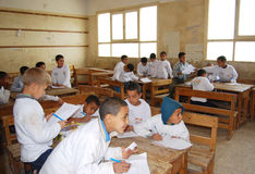 Students in class room during a lesson at school. Students in class room on wooden desks during a lesson at school while teacher writing Arabic words and letters Royalty Free Stock Images