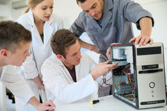 Students in a class with teacher repairing hardware Royalty Free Stock Images