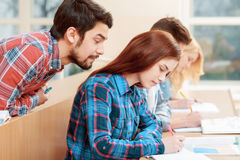Students at classes. Cheating on test. Young bearded male student peeping to the test-book of his female classmate sitting one desk before him Stock Images