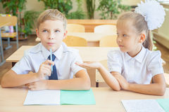 Students or classmates in school classroom sitting together at desk. Schoolboy thought, and girl helps him for the classwork. They are dressed in school Stock Image