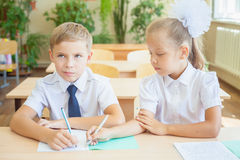Students or classmates in school classroom sitting together at desk Stock Images