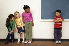 Students in Classroom. Students standing in classroom. A boy is separate from the girls. Horizontally framed shot Stock Photo