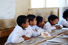 Students in classroom sitting on their disks. In USAID campaign to educate the poor children, behind them on wall some arabic words translations of the words Stock Photo