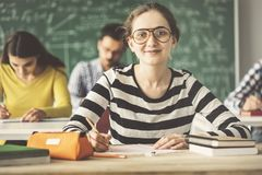 Students in classroom sitting and writing one of them smiling and looking camera Royalty Free Stock Image