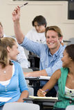 Students in classroom, teenage girls (16-18) looking at teenage boy (16-18) with arm raised Royalty Free Stock Photo