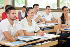 Students in classroom. Young students in classroom listening a lecturer Stock Image